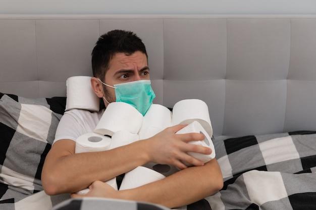 Un uomo si rallegra della carta igienica acquisita a causa del panico e della carenza causata dallo scoppio del virus covid19. un uomo usa una maschera protettiva, ha paura di ammalarsi.