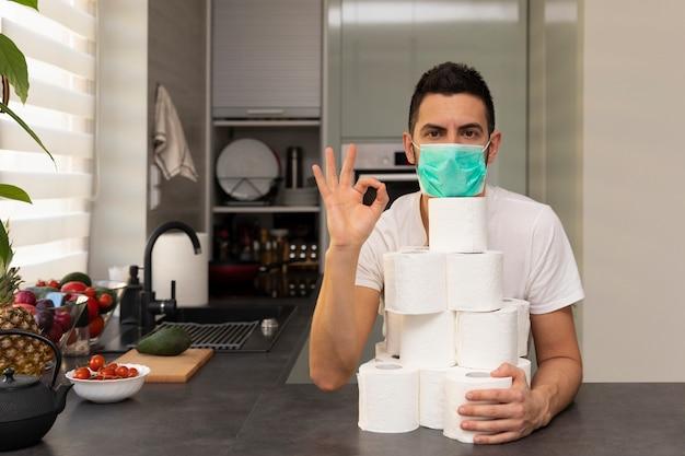 Un uomo si rallegra per la carta igienica, a causa del panico e della carenza causata dallo scoppio del virus covid19.