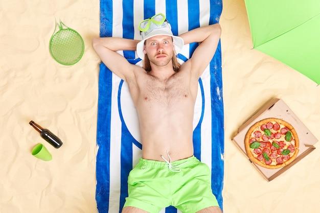 L'uomo si rilassa in spiaggia giace su un asciugamano a strisce blu mangia pizza beve birra indossa panama e pantaloncini prende il sole al sole si gode le vacanze