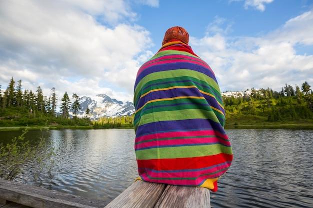 Uomo che si distende al bellissimo lago di montagne.