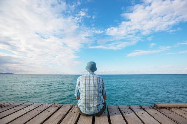 Uomo che si distende sul molo sul mare