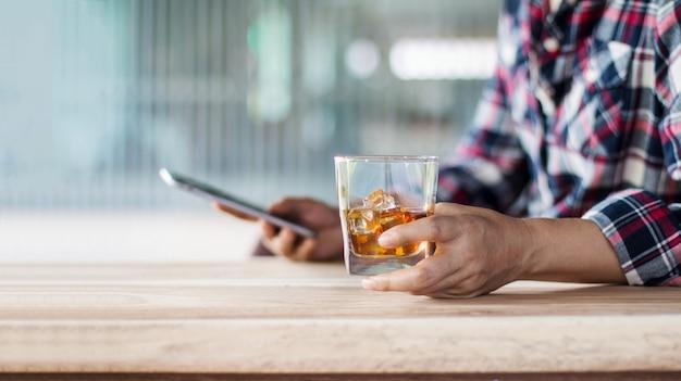 Uomo che si rilassa con una bevanda di whisky di bourbon
