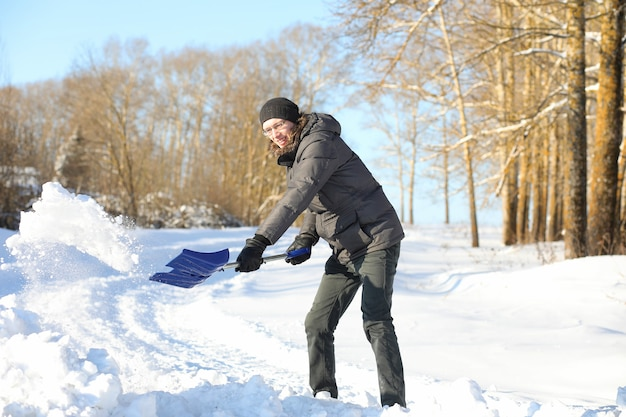 L'uomo rimuove la neve con la pala dalla strada in una giornata invernale