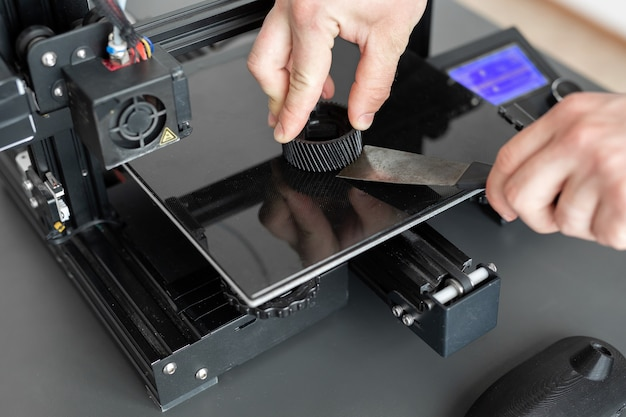 L'uomo rimuove la parte finita da una stampante 3d