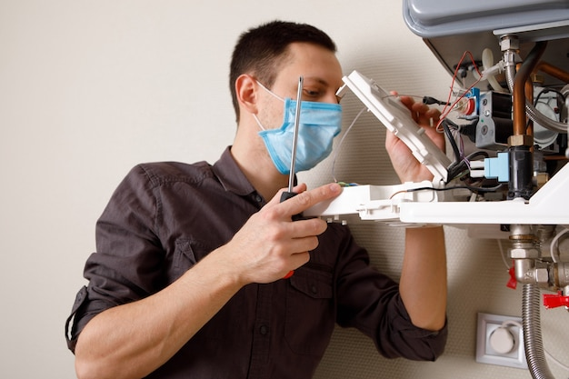 Un uomo che ripara una caldaia in una mascherina medica