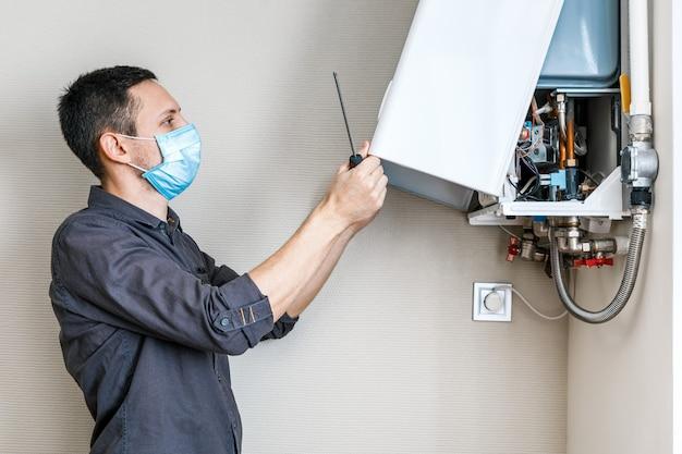Un uomo che ripara una caldaia in una mascherina medica Foto Premium