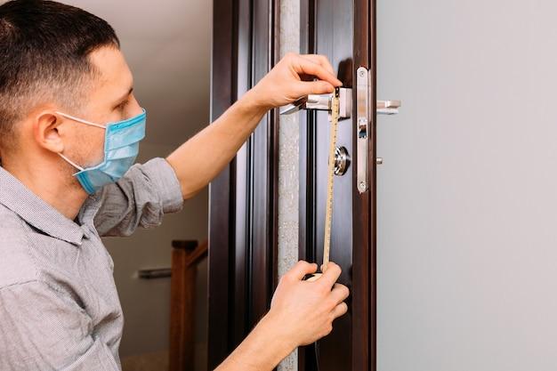 Uomo che ripara la maniglia. primo piano delle mani del lavoratore che installano il nuovo armadietto della porta