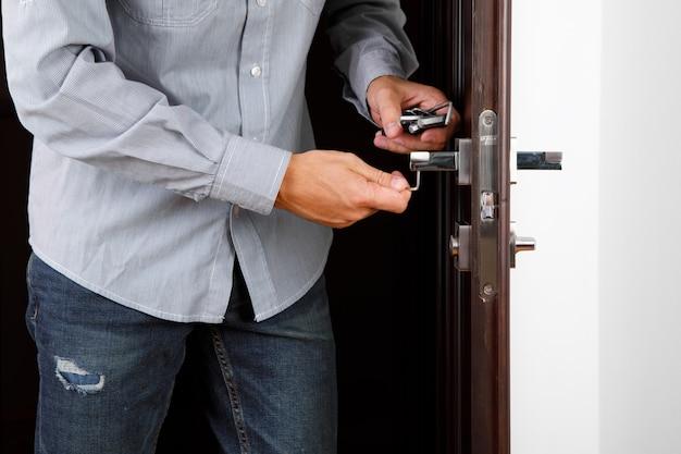 Uomo che ripara la maniglia. primo piano delle mani del lavoratore che installano un nuovo armadietto della porta