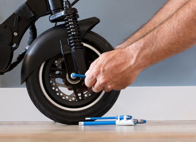 L'uomo ripara e regola lo scooter elettrico