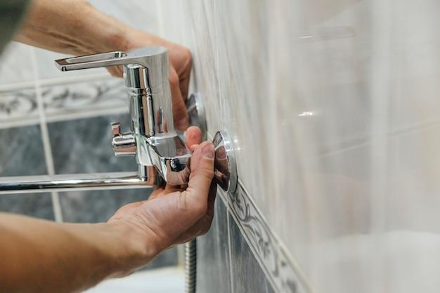Un uomo ripara un rubinetto in bagno