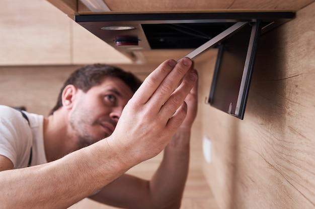 L'uomo ripara il cappuccio in cucina. filtro di ricambio nella cappa