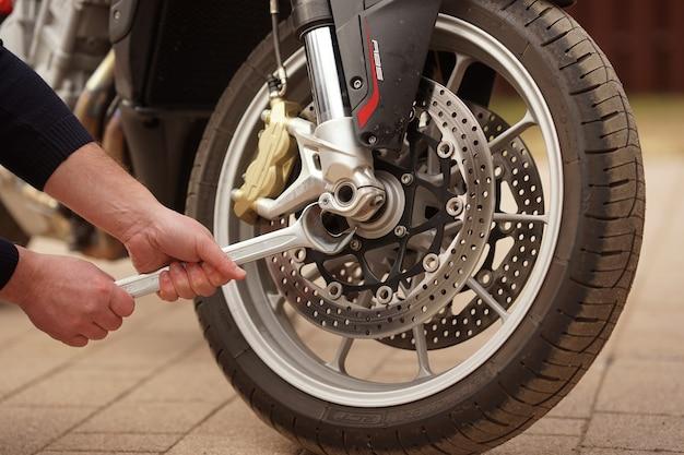 Un uomo ripara la motocicletta in servizio