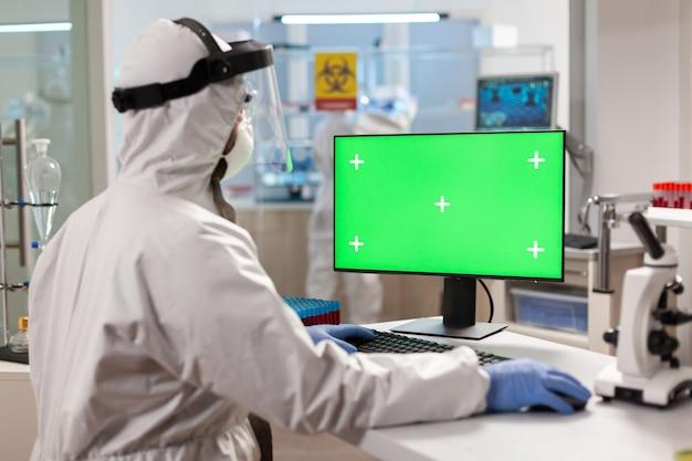 Ricercatore uomo in tuta che guarda il computer chroma key in un moderno laboratorio attrezzato