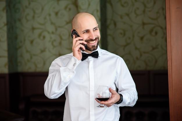 Un uomo in un ristorante che parla al telefono.