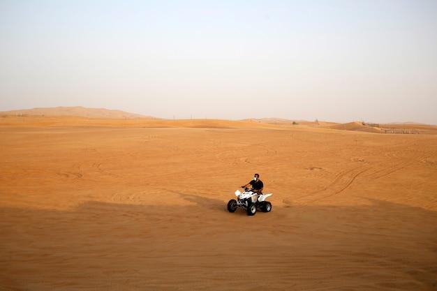 L'uomo cavalca un quad buggy sulla sabbia del deserto indossa una maschera facciale durante la quarantena
