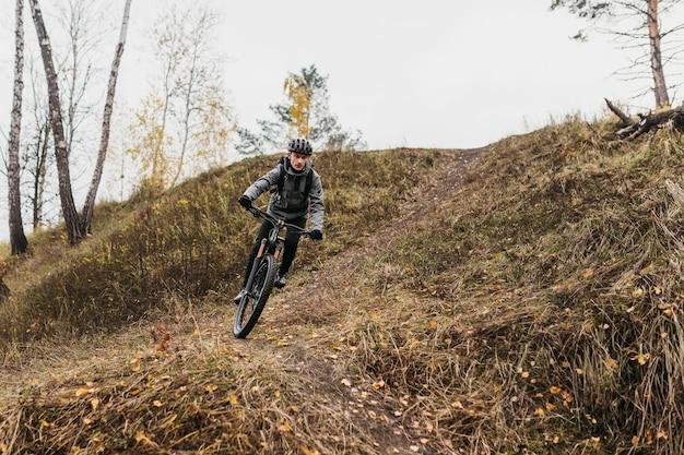 Uomo in sella a una bicicletta sul sentiero di montagna