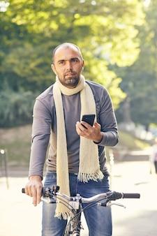 Uomo che guida la bici all'aperto - bel ragazzo giovane prendendo una bicicletta da giro e sorridente - look autunno vintage