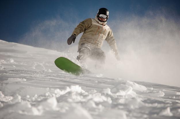 Uomo che guida giù per la collina con lo snowboard nella famosa località turistica di gudauri in georgia