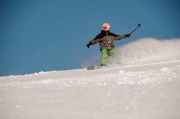 Uomo che guida giù per la collina con lo snowboard con la fotocamera in mano nella famosa località turistica di gudauri in georgia