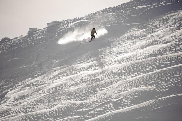 Uomo che cavalca giù per la collina coperta di neve con lo snowboard nella famosa località turistica di gudauri in georgia