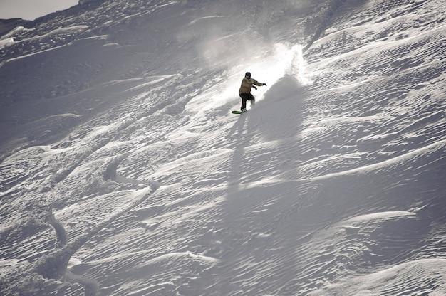 Uomo che guida giù per la collina coperta di neve bianca con lo snowboard nella famosa località turistica di gudauri in georgia