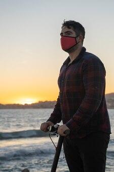 Uomo in sella al suo scooter elettrico al tramonto sul mare a palma de mallorca, spagna (verticale)