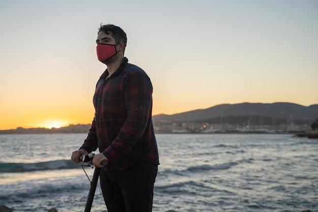 Uomo in sella al suo scooter elettrico al tramonto sul mare a palma de mallorca, spain