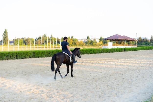 Uomo che monta un cavallo in pista