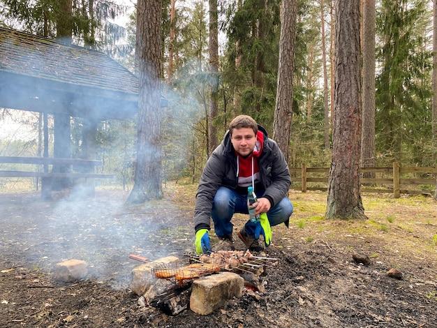 Un uomo arrostisce carne di maiale e pollo shish kebab su un falò in natura