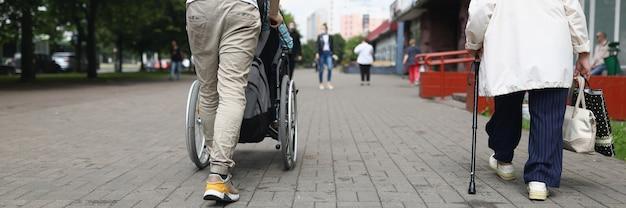 L'uomo fa rotolare una donna seduta su una sedia a rotelle per strada in città