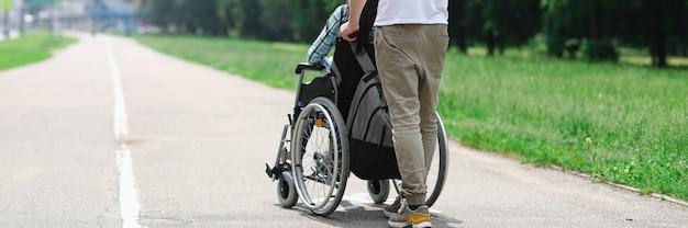 L'uomo rotola la sedia a rotelle con la ragazza per strada.