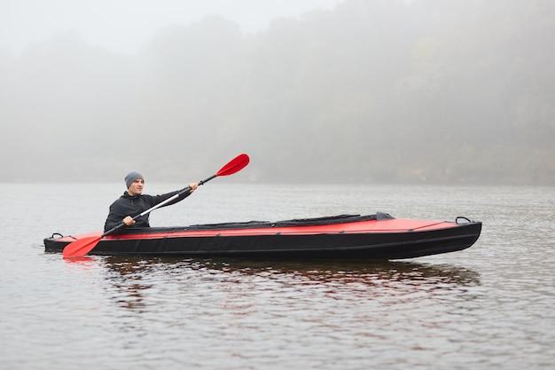 Uomo barca a remi in mattinata nebbiosa, tenendo in mano il remo rosso, godendosi il kayak, trascorrendo il suo tempo libero in modo attivo