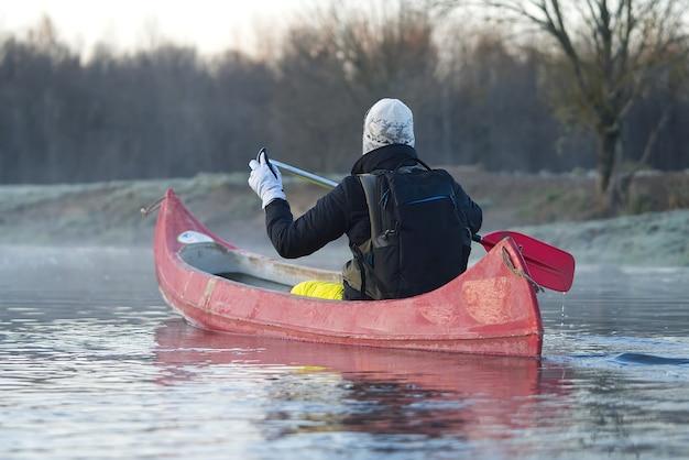 Uomo che rema una canoa all'inizio della primavera nella nebbia del paesaggio mattutino dello stile di vita mattutino vicino al fiume mattutino e delle persone sulla canoa