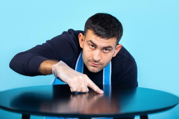 L'uomo in guanti di gomma si strofina con il dito e controlla la pulizia del tavolo