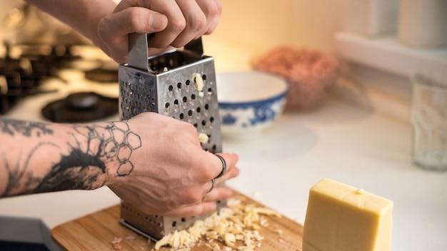 Uomo che strofina il formaggio su una grattugia