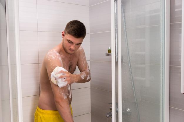 Uomo che si strofina una spugna da bagno in schiuma mentre si trova nella cabina doccia con porte in vetro trasparente in bagno
