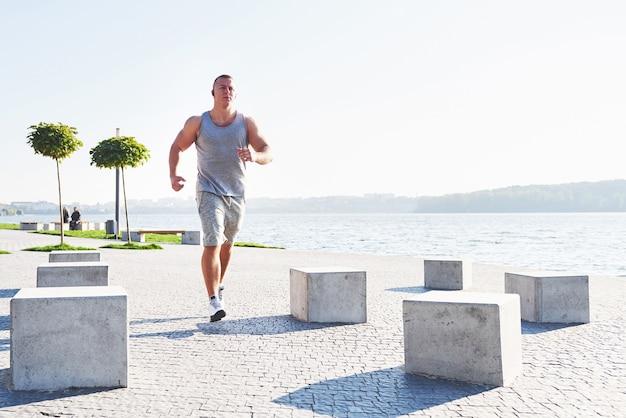 Corridore dell'uomo che fa esercizio di stretching, preparando per l'allenamento mattutino nel parco.