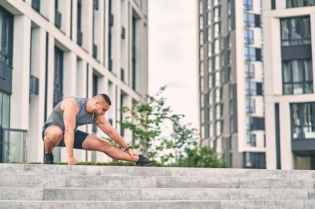 Corridore dell'uomo che impasta le gambe facendo stretching prima dell'allenamento stando in piedi sulle scale in strada