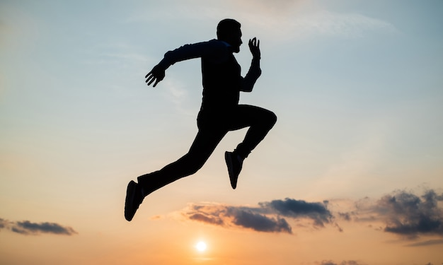 Siluetta del corridore dell'uomo che corre verso il futuro contro il cielo al tramonto, successo.