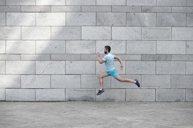 Uomo che corre all'aperto. corridore maschio sano. sbrigati. ritratto integrale del ragazzo di forma fisica in esecuzione. raggiungimento del successo e dell'eccellenza. atleta in esecuzione contro il muro di cemento. l'uomo sportivo inizia a correre.