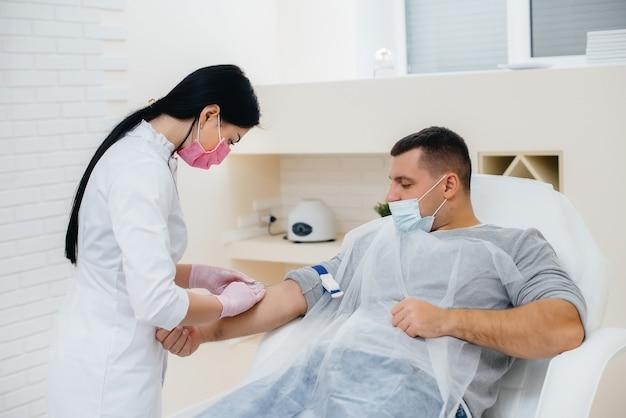 Il sangue di un uomo viene prelevato da una vena per l'analisi e il test per i virus. la formazione del sistema immunitario e degli anticorpi.