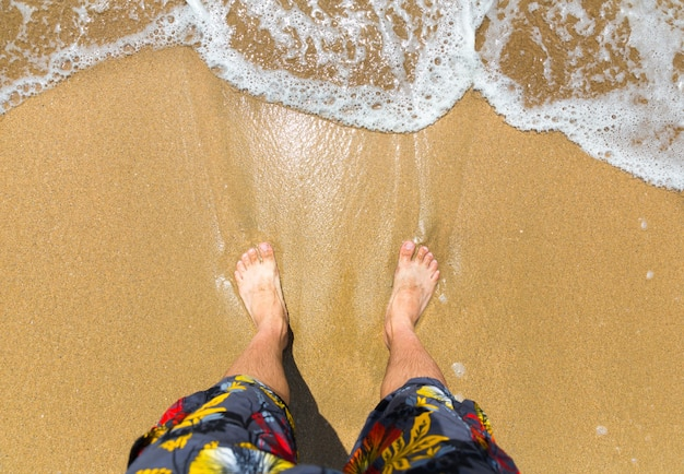 Piedi dell'uomo sulla spiaggia