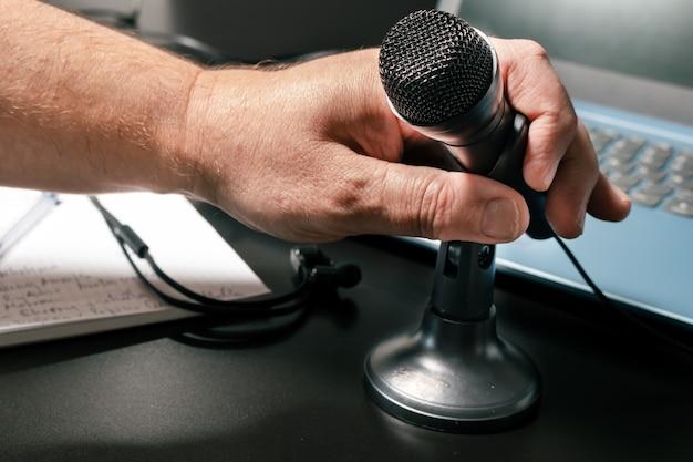 La mano di un uomo che ospita un microfono da tavolo prima di una conferenza virtuale. stile moderno,