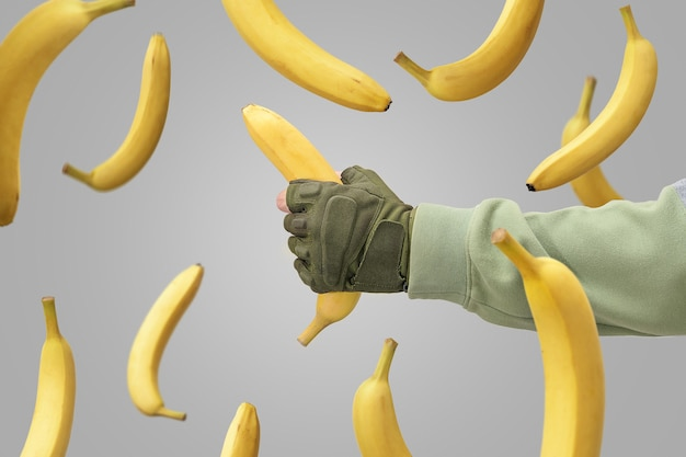 La mano di un uomo ha catturato una banana che cadeva. banane che cadono su uno sfondo grigio.