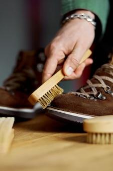 La mano dell'uomo pulisce le scarpe scamosciate con la spazzola