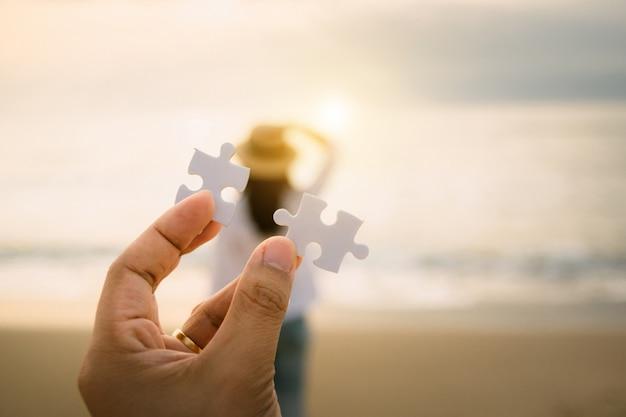 La mano dell'uomo dentro per collegare l'amore di concetto del pezzo di puzzle sulla donna sul retro la relazione una coppia