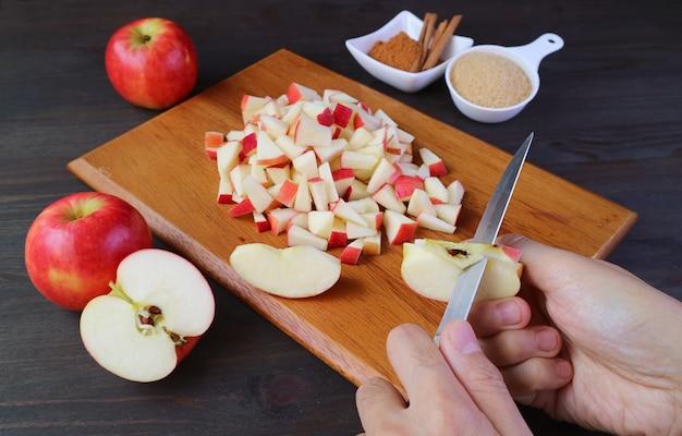 La mano dell'uomo taglia mele fresche con il coltello per fare la composta di mele