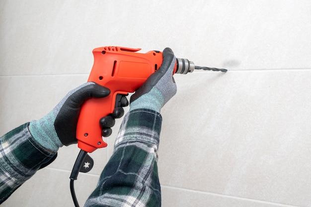 La mano di un uomo che perfora un buco nel muro con un trapano elettrico.