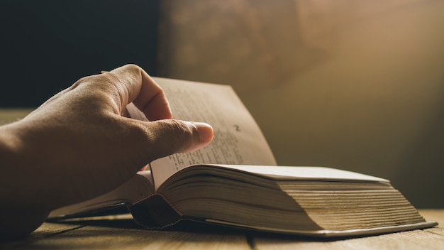 Mano dell'uomo che lancia la pagina del libro