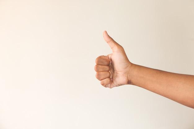 Mano della mano dell'uomo che mostra un pollice in su sul muro bianco.